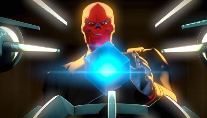 Imagem: cena da animação em que vemos o Caveira Vermelha, um homem com o rosto avermelhado e no formato de uma caveira, em um uniforme de militar nazista, segurando erguendo com luvas pretas um cubo azul e brilhante, e cercado por máquinas que apontam para o cubo com que prestes a extrair energia dele.