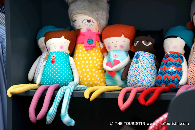 Eight colourful handmade dolls sitting on a wooden shelf, their spindly legs dangling in the air.