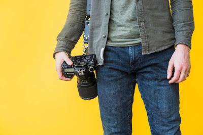 fotografer memegang kamera, tips membuat foto tajam