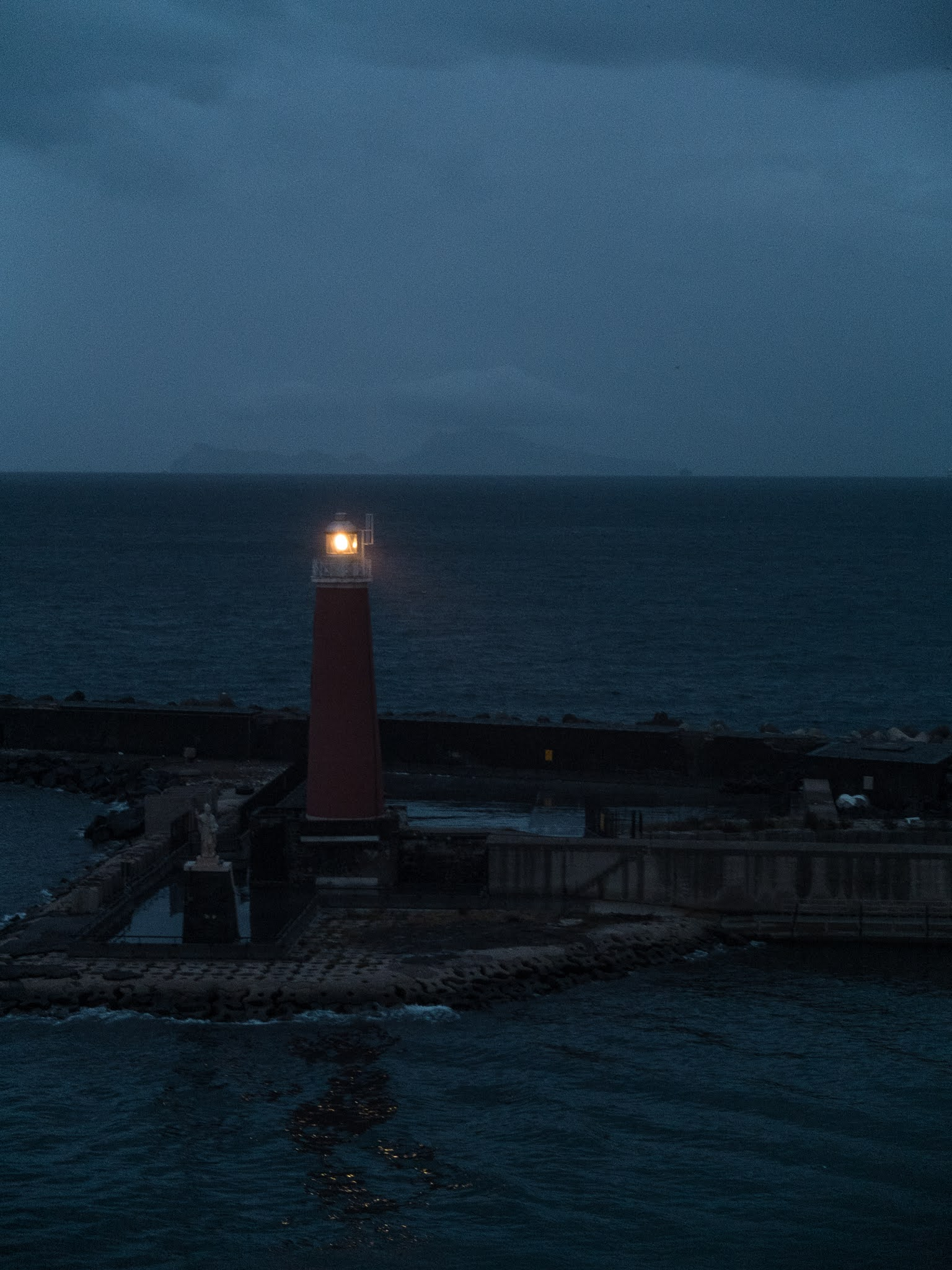 Molo San Vincenzo Lighthouse in the Port of Naples photographed at dusk.