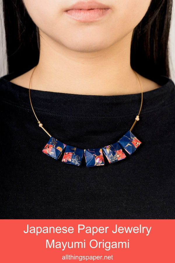 squares of folded floral patterned paper assembled into a necklace on model