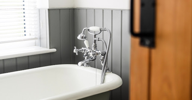 Clawfoot bathtub with faucet and hand shower.
