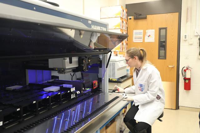 Camille Alba using a Microlab STAR precision liquid handling robot.