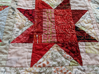 Quilting on the red sawtooth star reflects the flower motif in the background of the LeMoyne Stars