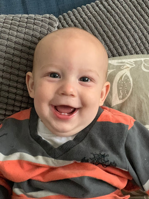 A 5 month old baby boy smiling and showing off his two bottom teeth