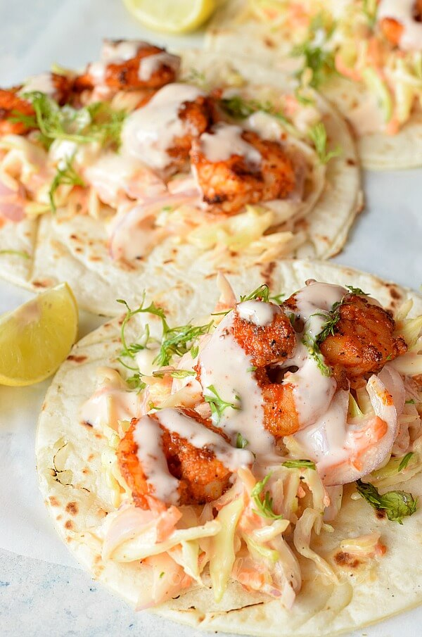 a white background with tortilla topped with cabbage cilantro lime slaw and spicy shrimp topped  with sriracha sauce