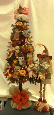 A small tree decorated with fall-themed decor and a scarecrow doll standing next to it.