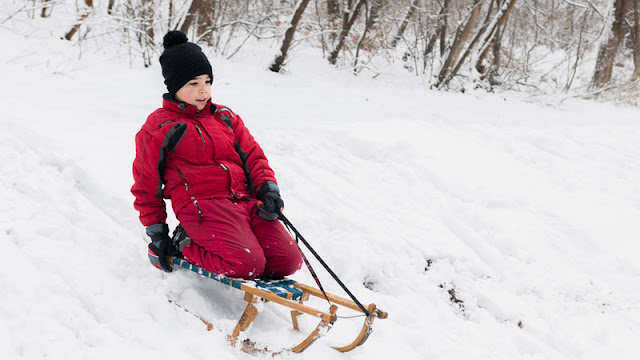 child in a red snow suit sledding down a hill