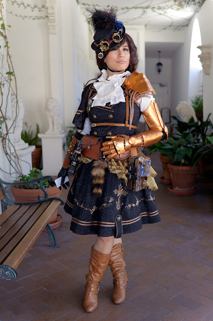 Female cosplayer in steampunk dress/jumper with white blouse, tan harness, tan leather boots, hat, goggles, and copper mechanical arm/gauntlet