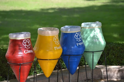 Four trash collection jars, color-coded and labeled for glass, plastic, paper, and metal.