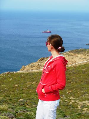 Moda dziweczyna w czerwonej bluzie spogláda na greckie błękitne morze.