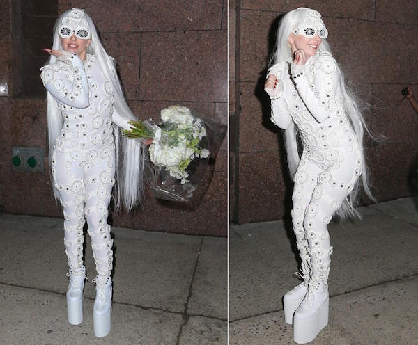 This pop star is covered head to toe in a white costume with her high footwears.