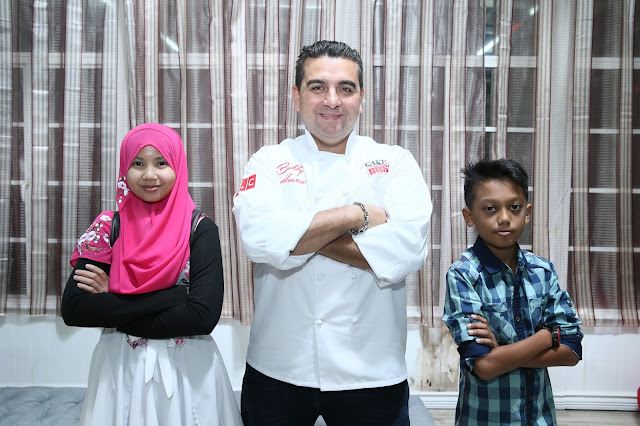 Buddy posing with Fathul and Najiha of the Make A Wish Foundation