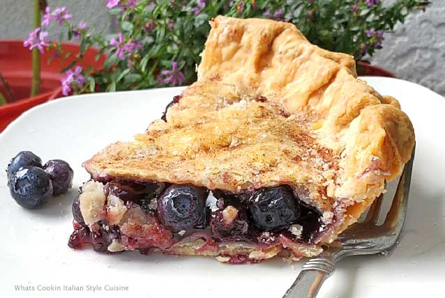this is a sliced of homemade blueberry pie on a white plate