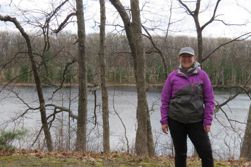 hiker standing with lake in background