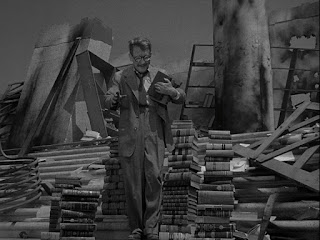 A picture of Burgess Meredith in a Twilight Zone Episode on stairs surrounded by books.