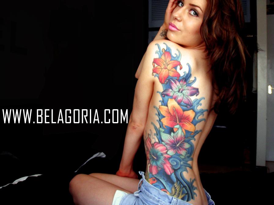 una modelo sentada vemos sus tatuajes de flores en las costillas