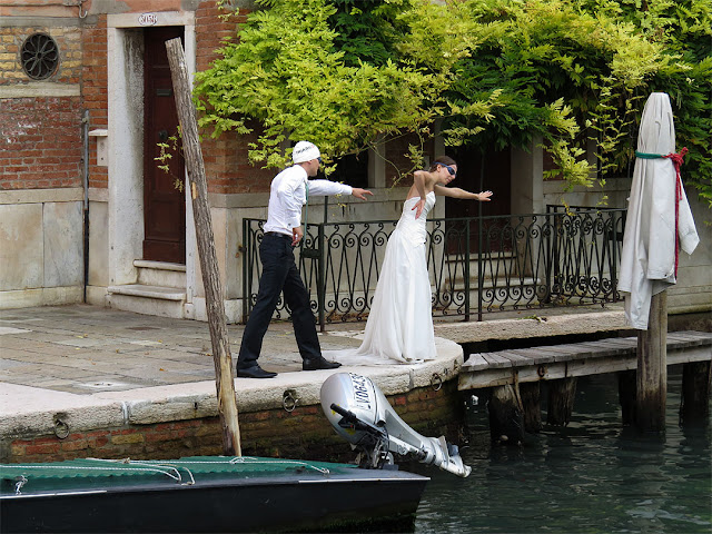 Bride and groom swim for the photographer, Rio di San Lorenzo, Castello, Venice