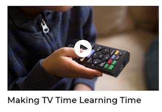 Child holding a remote and pointing it toward a television
