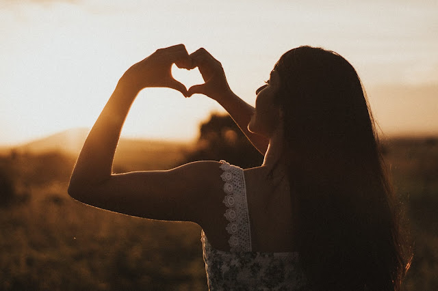 A woman holding her hands in a heart shape at the sunset