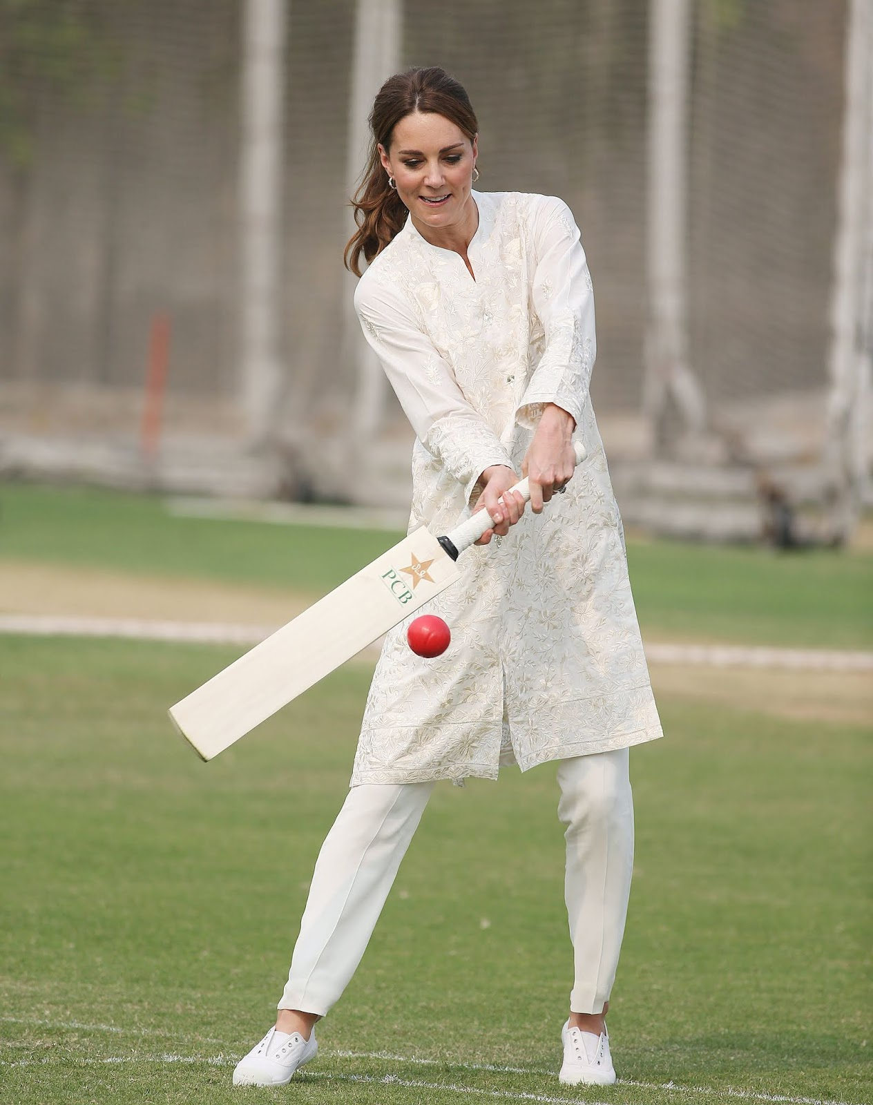 Britain's Prince William and Duchess of Cambridge Kate Middleton play cricket at the National Cricket academy in Lahore