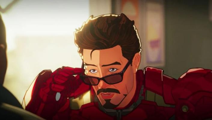Imagem: o personagem Tony Stark, sentado em uma mesa de um restaurante com o seu traje de Homem de Ferro.