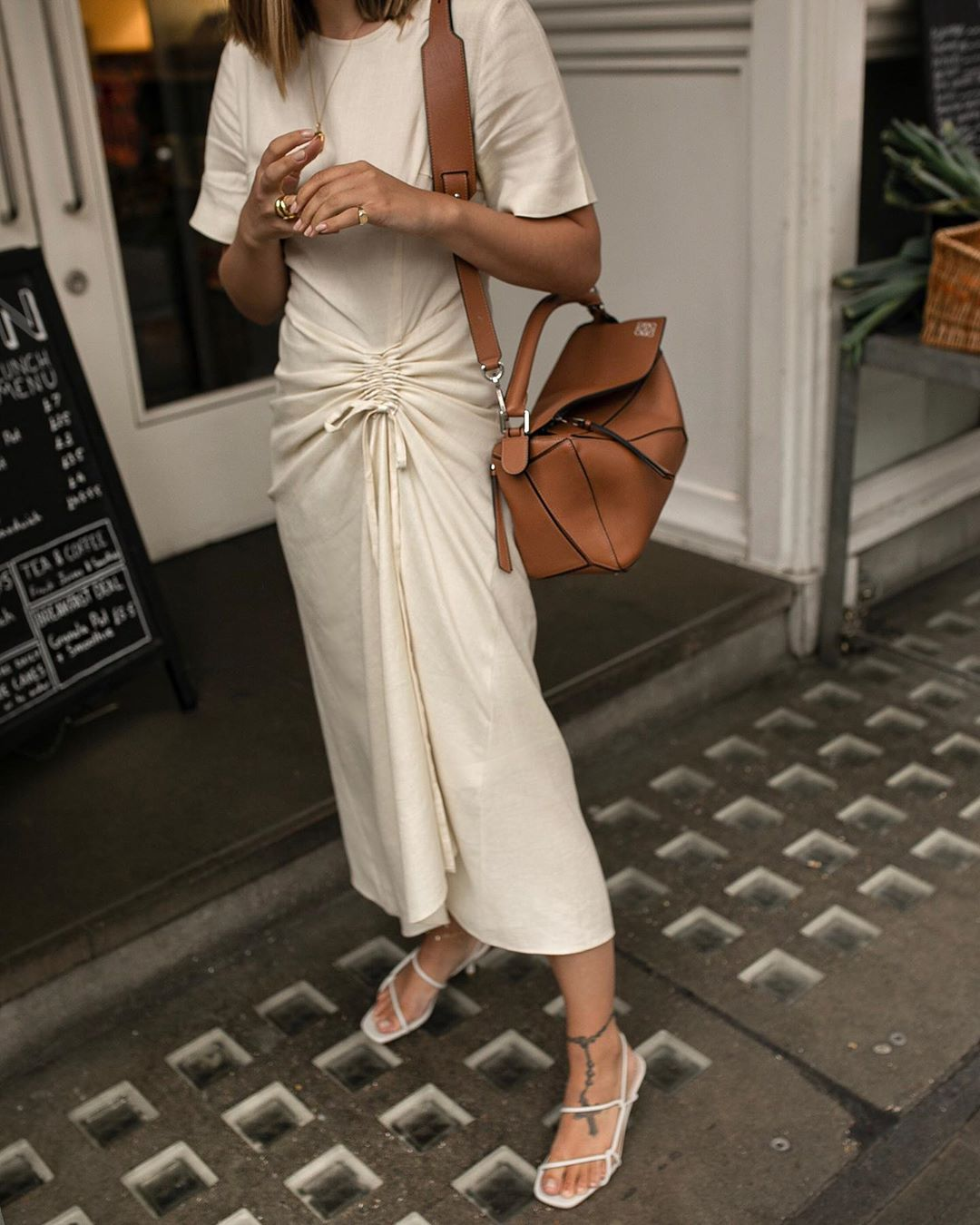 Spring / Summer Instagram Outfit Idea — Beige Ruched Dress, Camel Loewe Puzzle Bag, and Strappy White Sandals