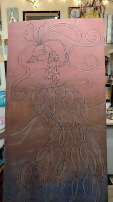 ink drawing of a peacock on underlayment wood