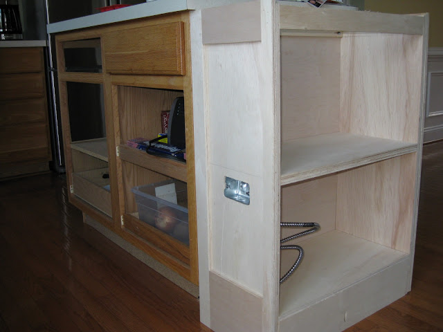 a playwood shelf is added to one end of a kitchen island.