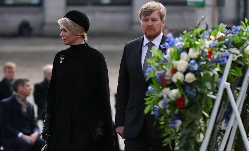 Queen Maxima wore a black wool high collar cape coat. Black leather handbag. Pearl drop earrings and diamond brooch. Gripoix earrings