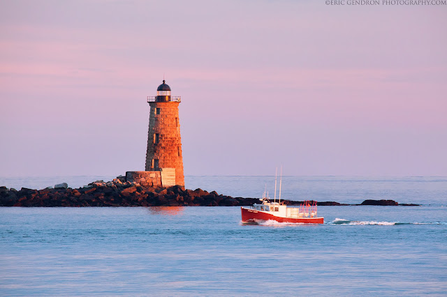 A fishing boat passing by whaleback lighthouse