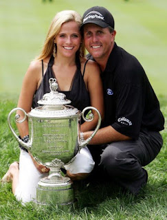 Amy and her husband Phil taking a photo of themselves with a trophy