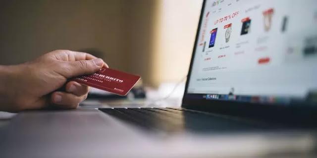 Mano que sostiene la tarjeta de crédito frente a una computadora portátil