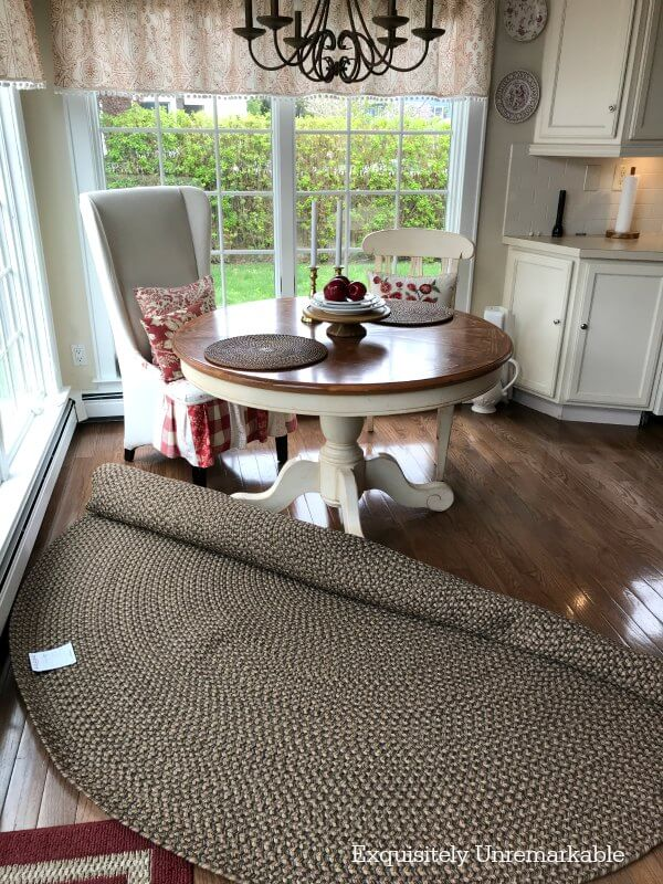 Braided rug half unrolled under round table in the kitchen