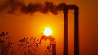 Smokestacks at sunset (Credit: Reuters) Click to Enlarge.
