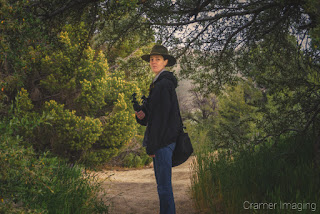 Behind-the-scenes photograph of landscape photographer Audrey Cramer looking back up the trail