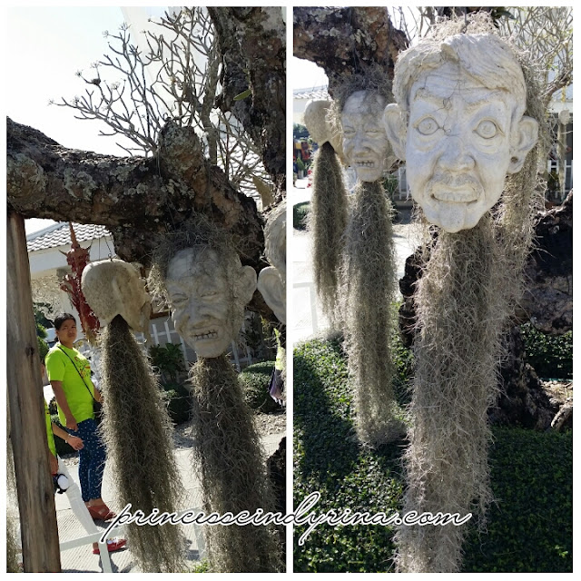 stone heads hanging from trees