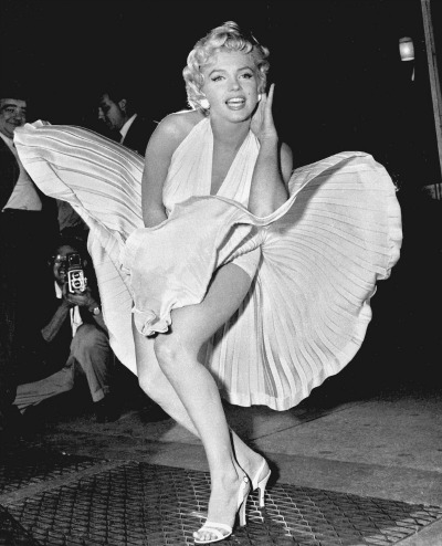 Marilyn Monroe in scene from Seven Year Itch where white dress billows around her showing her legs