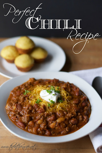 The finished bowl of chili with a plate of cornbread muffins in the back and the title above.