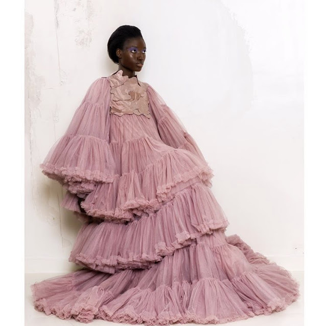 A model posing in a pink dress.