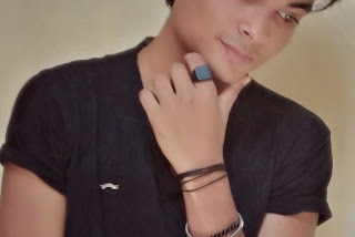 A boy wearing a black,square face ring