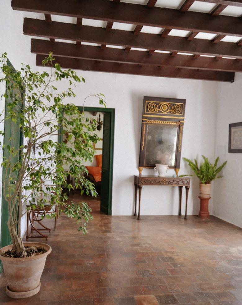 Decoración de una gran entrada, un hall con diferentes espacios y mezcla de muebles antiguos