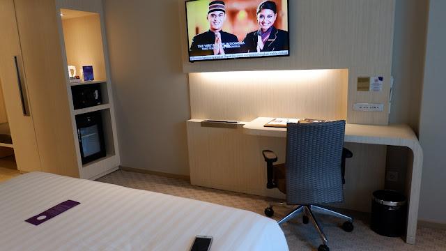 ada televisi dan meja kerja di kamar hotel