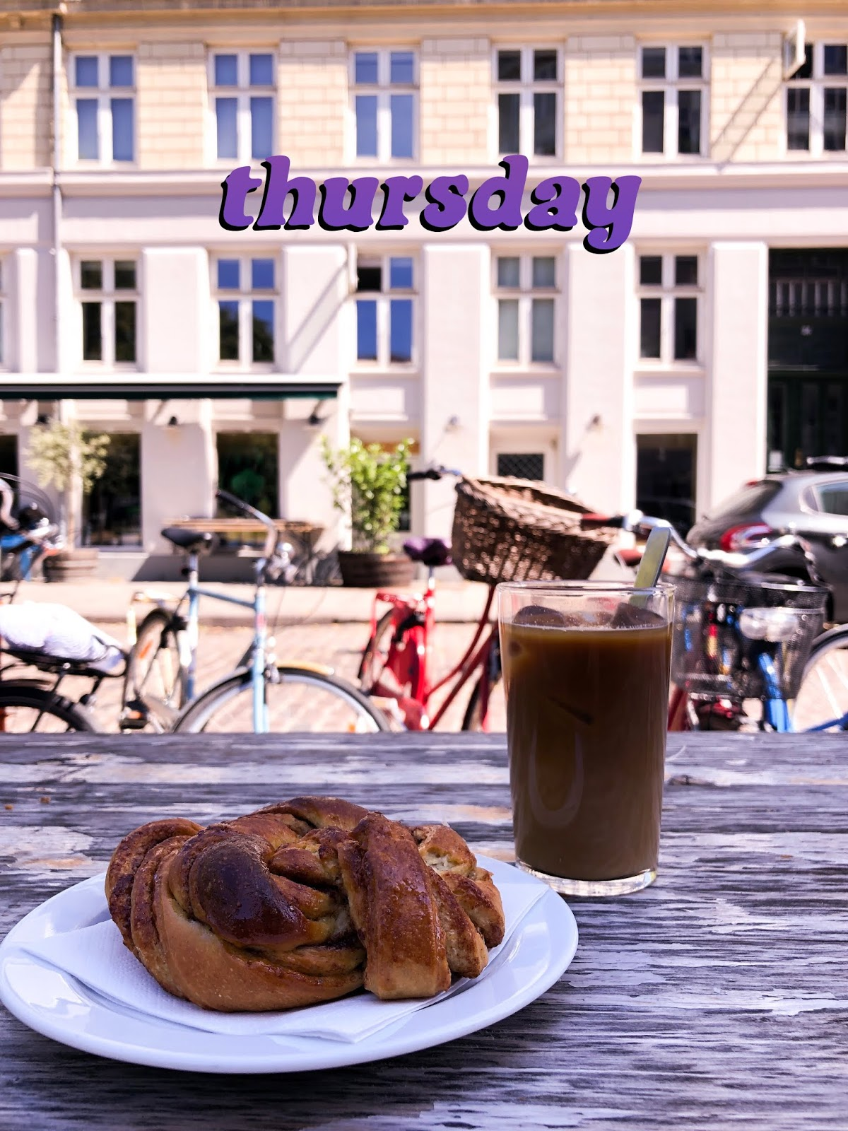 iced latte and cinnamon pastry on table on jaegersborgge street Copenhagen with bikes lined up in background
