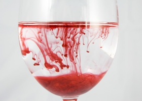 Red ink dissolving in a glass of water.