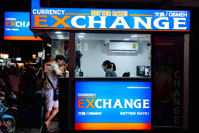 Man at currency exchange booth making transaction