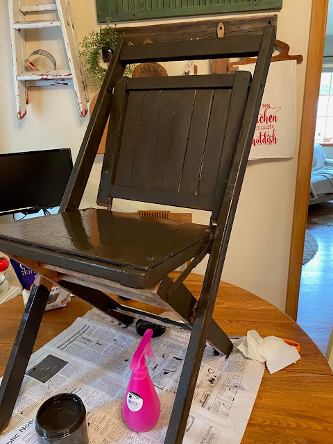 Photo of a wooden folding chair being painted in coffee bean paint