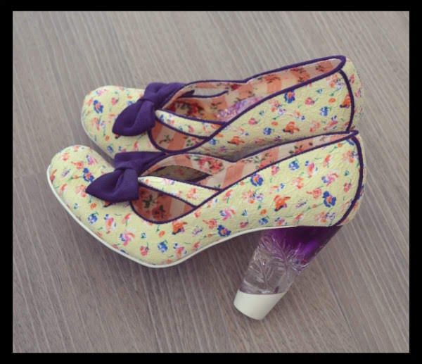 cream floral shoes with purple bow and perspex heel sitting on floor