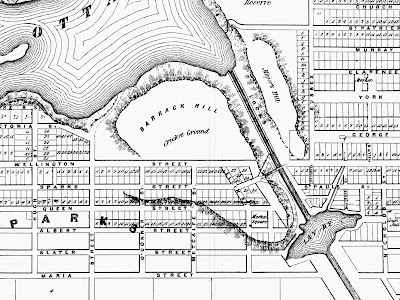 Crop of an 1856 black and white map of Ottawa with extents Hugh (Kent, West), Ottawa River and Church/St.Patrick Street (North), Nicholds (Nicholas, East), and Maria (Laurier, South). Centred in the section is Barrack Hill, on the west bank along the firs teight locks of the canal, also labelled Cricket Ground in smaller print. The outline of the hill extends along the Rideau Canal as far south as Slater Street, before curving west and back up toward Queen and Metcalfe. East of the canal opposite Barrack Hill is Major's Hill. Just south of this hill is the Lay By, a basin in the canal. Streets are drawn and named, and properties are indicated and many are numbered sequentially, bu tonly as far south as Albert Street. Wellington Street goes up to the edge of the hill but not down it, nor across the Canal. Sparks Street crosses Elgin Street and meets the west abutment of the Sapper's Bridge, which crosses the Rideau Canal and meets the west end of Rideau Street.