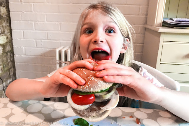My daughter pulling a funny face, about to bite into the loaded burger as the contents falls out on the table and plate.